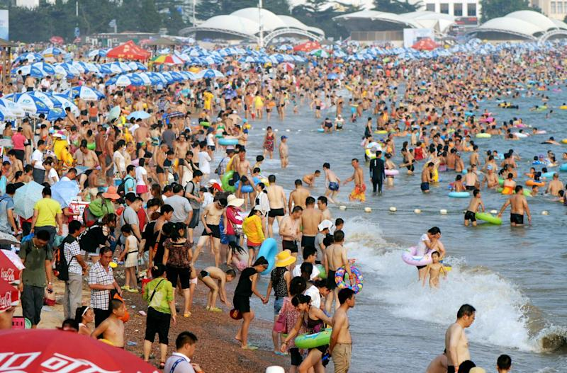 People gather to cool off on a beach in Qingdao, in eastern Shandong province, as a record-setting summer heat wave hit much of China, on August 8, 2013