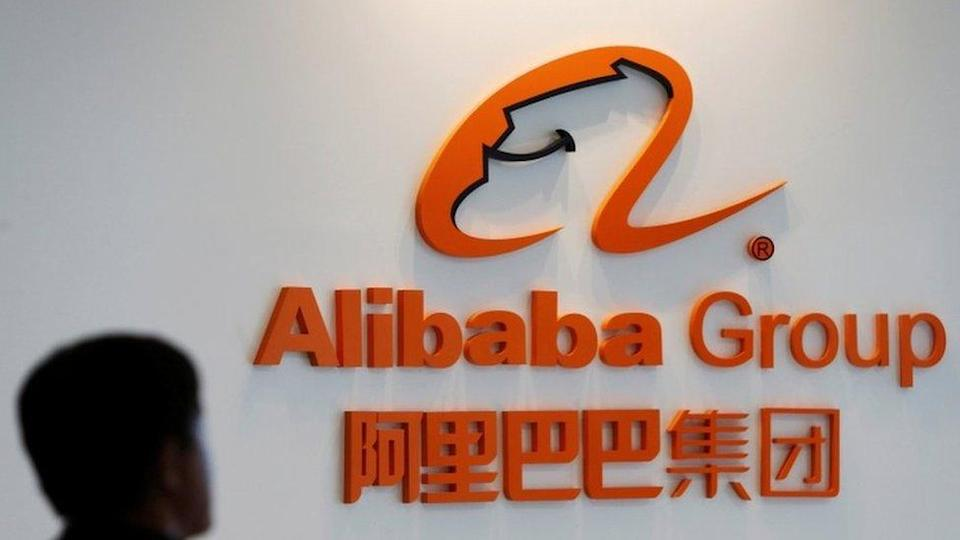 """A man stands near the logo of Alibaba Group at the company""""s newly-launched office in Kuala Lumpur"""