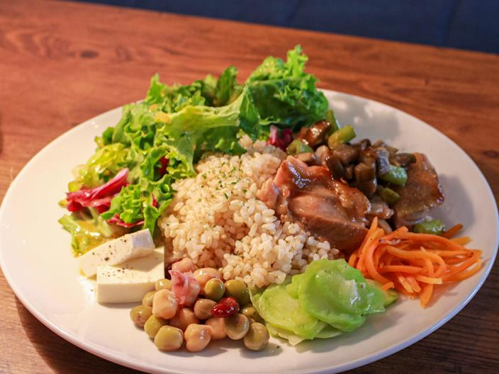 A white plate with rice, beans, salad, cheese, and sautéed chicken.