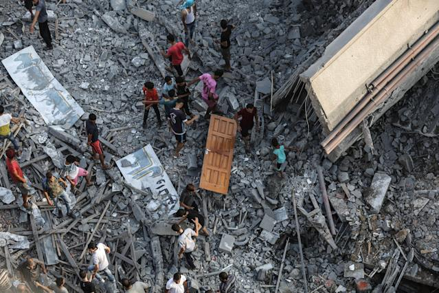 <p>People inspect the debris of Said Al-Mashal Foundation for Arts and Culture building after Israeli forces conducted airstrikes with at least ten rockets targeted the cultural center, in western part of Gaza City, Gaza on Aug. 9, 2018. (Photo: Ali Jadallah/Anadolu Agency/Getty Images) </p>