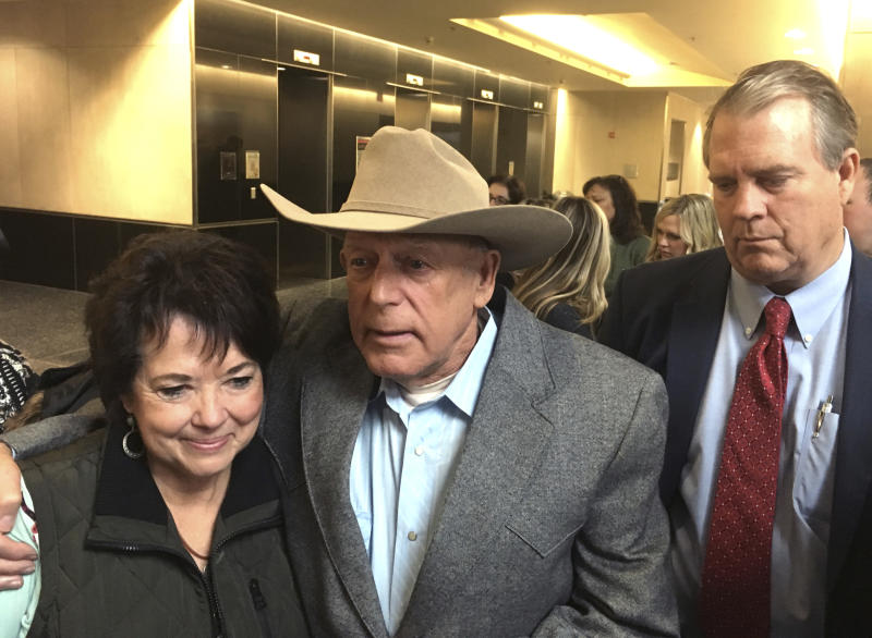 Rancher and states' rights figure Cliven Bundy, center, emerges from court on Monday, Jan. 8, 2018, a free man, flanked by his wife, Carol Bundy, left, and attorney Bret Whipple, right, at the U.S. District Court building in Las Vegas. The 71-year-old Bundy was freed from federal jail custody after a U.S. judge dismissed all charges against him, two sons and a Montana militia leader who were accused of leading an armed uprising against federal authority in April 2014. (AP Photo/Ken Ritter)