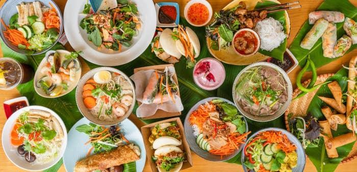 A large assortment of delicious and brightly colored Vietnamese dishes are spread on a table
