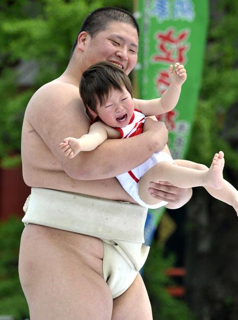 "A crying baby is carried by a student sumo wrestler during the ""Baby-cry Sumo"" competition at Tokyo's Sensoji temple on April 30, 2011.  Some 50 babies aged under one participated in the annual baby crying contest. Japanese parents believe that sumo wrestlers can help make babies cry out a wish to grow up with good health.   AFP PHOTO/Yoshikazu TSUNO"