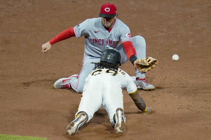 The throw from Cincinnati Reds catcher Tucker Barnhart gets past shortstop Kyle Farmer as Pittsburgh Pirates' Troy Stokes Jr. steals second during the sixth inning of a baseball game, Tuesday, May 11, 2021, in Pittsburgh. (AP Photo/Keith Srakocic)