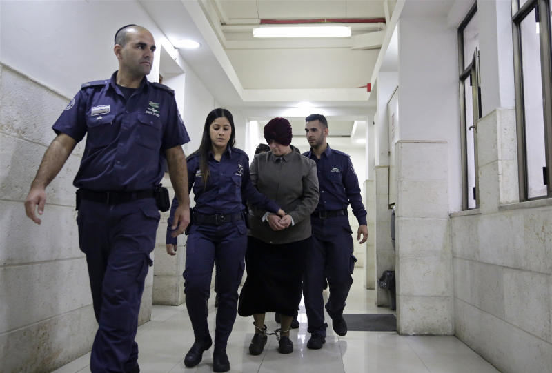 FILE - This Feb. 27, 2018 file photo, Australian Malka Leifer, center, is brought to a courtroom in Jerusalem. Leifer is wanted in Australia for 74 charges of sexual assault and the country's request for her extradition has been delayed for years. (AP Photo/Mahmoud Illean, File)