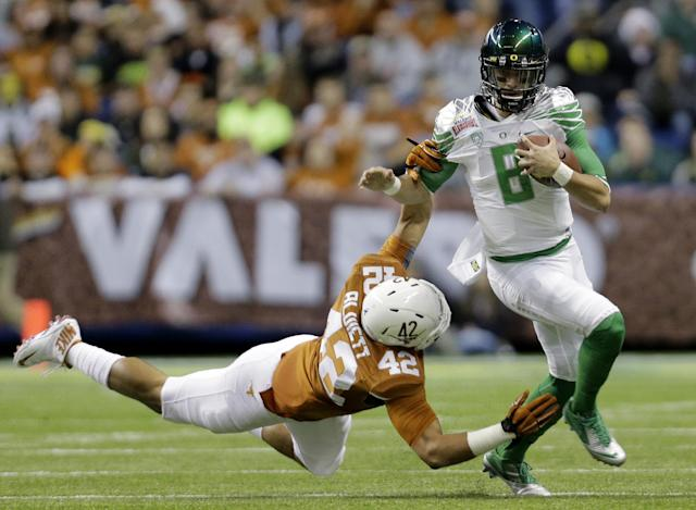 Oregon's Marcus Mariota (8) is pulled down by Texas' Caleb Bluiett (42) during the first quarter in the Valero Alamo Bowl NCAA college football game, Monday, Dec. 30, 2013, in San Antonio. (AP Photo/Eric Gay)