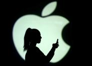 FILE PHOTO: Picture illustration of a silhouette of a mobile user next to a screen projection of the Apple logo