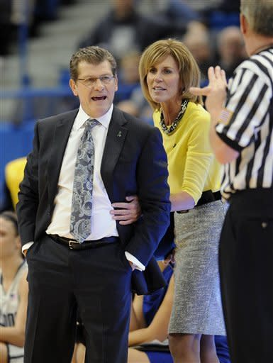 Connecticut head coach Geno Auriemma, left, is held back by associate head coach Chris Dailey, center, as he argues a call with an official during the first half of an NCAA college basketball game in Hartford, Conn., Tuesday, Jan. 15, 2013. (AP Photo/Jessica Hill)
