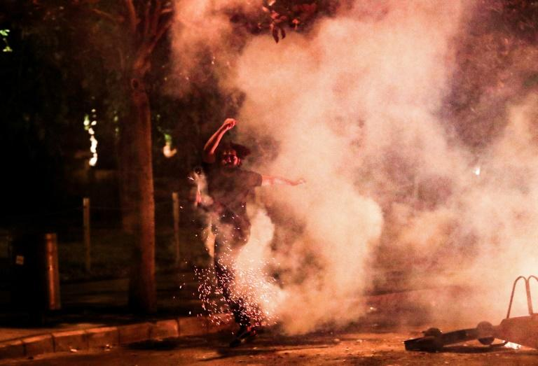 A Lebanese anti-government protester kicks back a tear gas canister fired by security forces during a protest against dire economic conditions in Beirut on Friday night (AFP Photo/ANWAR AMRO)