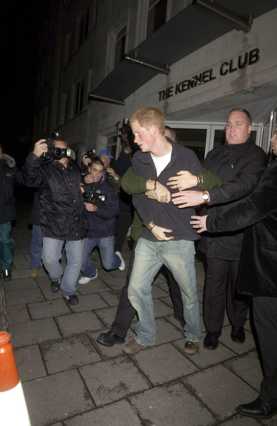 """<p>In 2004, Harry decided it was a good idea to get into a """"scuffle"""" with a group of photographers who were taking his picture as he was leaving a nightclub, and everyone ended up injured. """"Prince Harry was hit in the face by a camera as photographers crowded around him as he was getting into a car,"""" a spokesperson <a href=""""https://www.theguardian.com/media/2004/oct/21/pressandpublishing.themonarchy"""" rel=""""nofollow noopener"""" target=""""_blank"""" data-ylk=""""slk:said"""" class=""""link rapid-noclick-resp"""">said</a>. """"In pushing the camera away, it's understood that a photographer's lip was cut."""" </p>"""