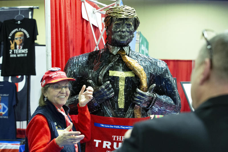 A supporter of President Trump poses for a photo next to a figure during Conservative Political Action Conference, CPAC 2020, at the National Harbor, in Oxon Hill, Md., Thursday, Feb. 27, 2020. (AP Photo/Jose Luis Magana)