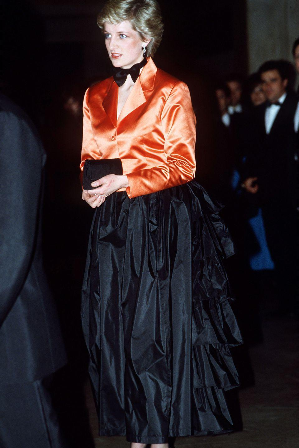 <p>In an orange jacket, black bow-tie and black evening skirt on an official visit to Lisbon, Portugal. </p>