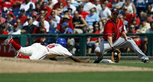 Philadelphia Phillies' Juan Pierre, left, slides safely into first as Washington Nationals' Adam LaRoche attempts a pick-off in the third inning of a baseball game, Sunday, Aug. 26, 2012, in Philadelphia. (AP Photo/H. Rumph Jr)