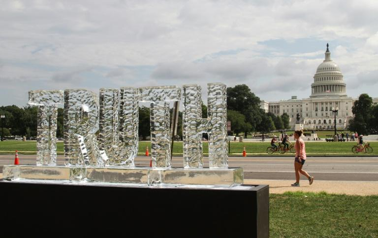 "A woman walks behind an ice sculpture spelling out the word ""truth"" by artist duo LigoranoReese, with the US Capitol in the background, in Washington on September 22, 2018"