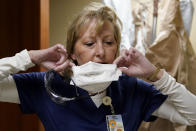 FILE - In this Nov. 24, 2020, file photo, marks are seen on the face of registered nurse Shelly Girardin as she removes a protective mask after performing rounds in a COVID-19 unit at Scotland County Hospital in Memphis, Mo. Across the U.S., the surge has swamped hospitals with patients and left nurses and other health care workers shorthanded and burned out. (AP Photo/Jeff Roberson)