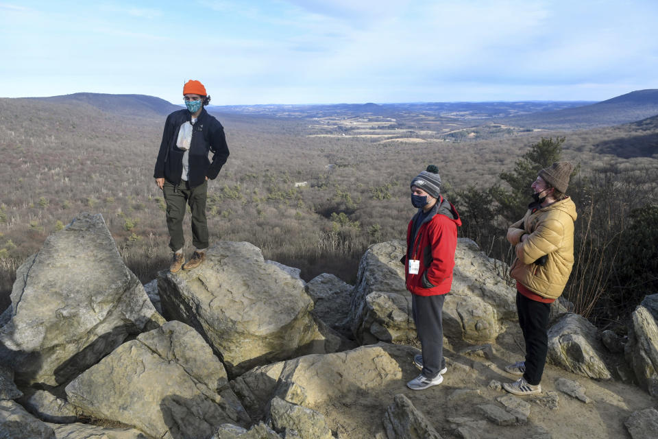 Keilan Barber, of West Chester, Pa., left, Christian Martella, center, and Ben Savitz, both of Havertown, Pa., hang out on the rocks at the South Lookout after hiking at Hawk Mountain Sanctuary in Kempton, Pa., in this Sunday, Jan. 24, 2021, file photo. During the pandemic, people around the world sought relief from lock downs and working from home in leisure sports.(Jacqueline Dormer/Republican-Herald via AP, File)