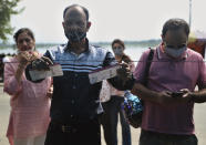 An Indian tourist shows his recent flight's boarding passes as proof of COVID-19 test as he waits to enter the Mughal garden on the outskirts of Srinagar, Indian controlled Kashmir, on Aug. 2, 2021. Tourists are returning to the valleys and mountains in Indian-controlled Kashmir, as infections in the Himalayan region and nationwide come down after a deadly second wave earlier this year. (AP Photo/Mukhtar Khan)