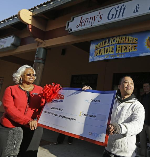 Jenny's Gift Shop owner Thuy Nguyen, right, accepts a $1 million check from California lottery sales representative Mona Sanders Wednesday, Dec. 18, 2013, in San Jose, Calif. Two lucky winning tickets were sold in Tuesday's near-record $636 million Mega Millions drawing: one at a tiny newsstand in Atlanta, and the other more than 2,000 miles away in California. huy Nguyen, says he doesn't know who the bought the winning ticket, but it's likely someone he knows, as most of his customers are his friends. (AP Photo/Ben Margot)