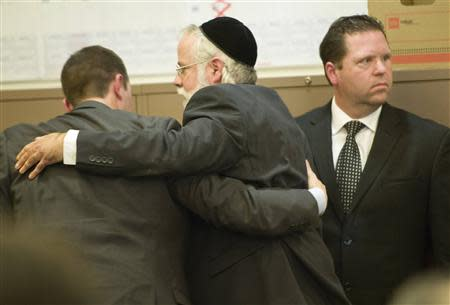 Former Fullerton police officer Jay Cicinelli (R) looks back into the court gallery as his attorney Michael Schwartz (C), embraces co-counsel after the not-guilty verdict is read in the Kelly Thomas murder trial in Santa Ana, California January 13, 2014. REUTERS/Mindy Schauer/Pool