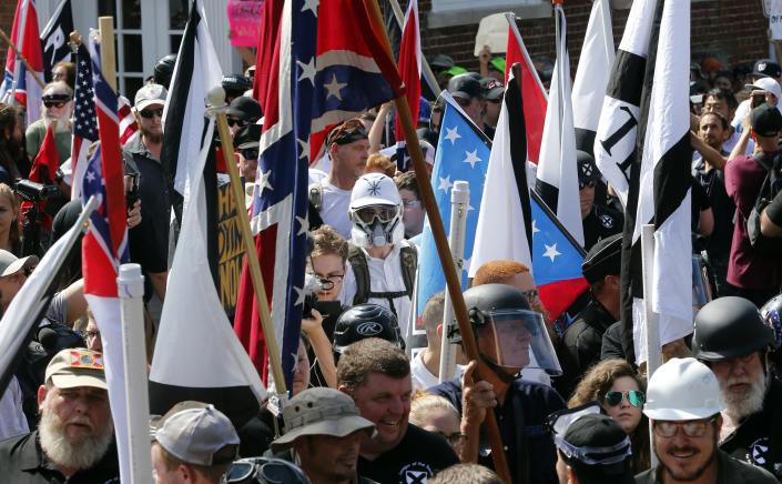 <p>White nationalist demonstrators walk into the entrance of Lee Park surrounded by counter demonstrators in Charlottesville, Va., Saturday, Aug. 12, 2017. (Photo: Steve Helber/AP) </p>