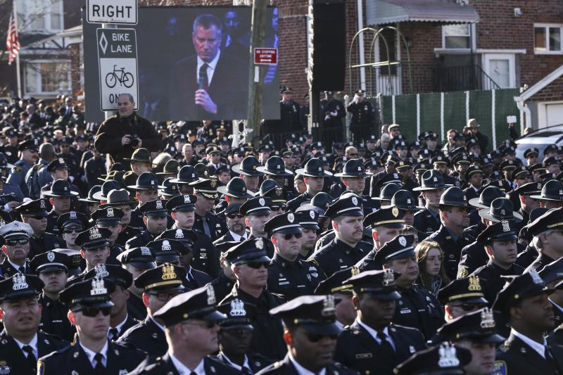 Law enforcement officers turn their backs on a live video monitor showing New York City Mayor Bill de Blasio as he speaks at the funeral of slain New York Police Department (NYPD) officer Rafael Ramos near Christ Tabernacle Church in the Queens borough of New York December 27, 2014. Tens of thousands of police and other mourners filled a New York City church and surrounding streets for the funeral on Saturday of one of two police officers ambushed by a gunman who said he was avenging the killing of unarmed black men by police. Singled out for their uniforms, the deaths of Rafael Ramos and his partner Wenjian Liu have become a rallying point for police and their supporters around the country, beleaguered by months of street rallies by protesters who say police practices are marked by racism.   REUTERS/Shannon Stapleton   (UNITED STATES - Tags: CIVIL UNREST POLITICS CRIME LAW TPX IMAGES OF THE DAY)