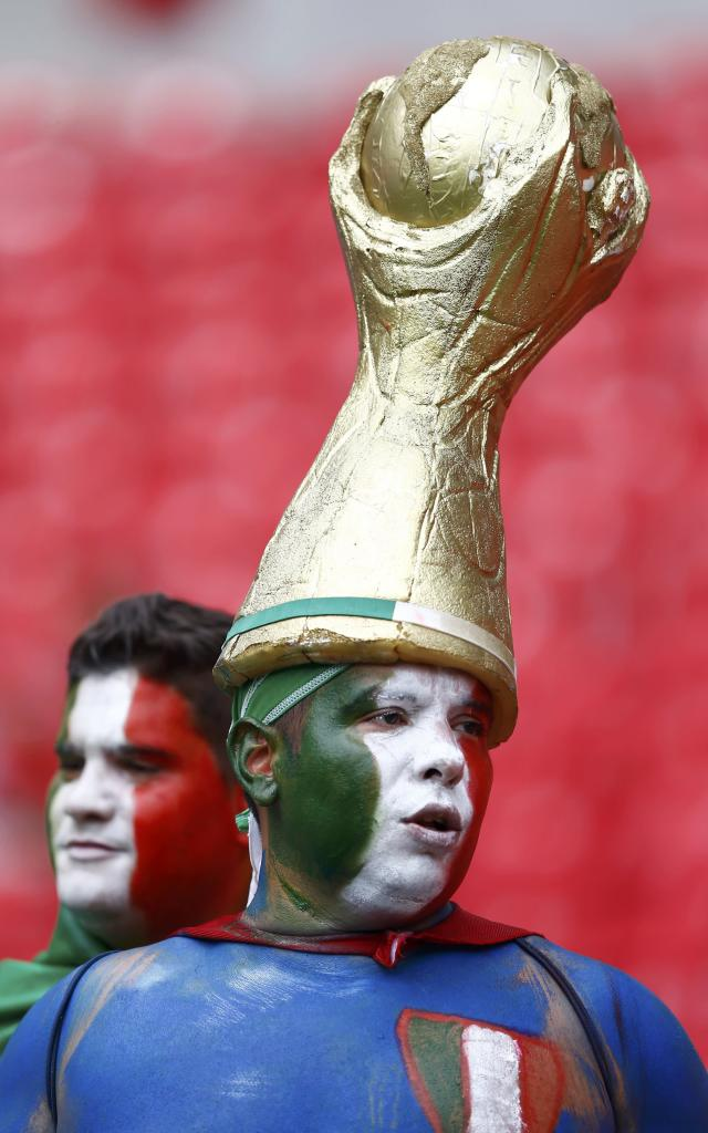 A fan of Italy wears a hat decorated with a replica of the World Cup trophy before their 2014 World Cup Group D soccer match against Costa Rica at the Pernambuco arena in Recife June 20, 2014. REUTERS/Dominic Ebenbichler (BRAZIL - Tags: SOCCER SPORT WORLD CUP)