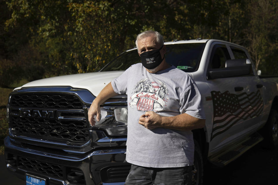 Anthony Starkey, a retired coal miner, stands beside his truck in Danville, W.Va., on Tuesday, Oct. 13, 2020. Starkey said President Donald Trump earned his vote again by signing a bill last year to save the pensions of some retired coal workers, including his own. (AP Photo/Chris Jackson)
