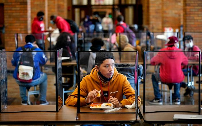 Freshman Hugo Bautista eats lunch separated from classmates by plastic dividers at Wyandotte County High School in Kansas City - Charlie Riedel/AP