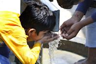 NOIDA, INDIA - JUNE 9: A boy drinks water from a hand pump, at sector 14-A, on June 9, 2019 in Noida, India. The national capital reeled under scorching heat Saturday, with high humidity adding to the discomfort of the residents. Delhi is expected to record a high of 44 and a low of 29 degrees Celsius, a MeT official said. (Photo by Sunil Ghosh/Hindustan Times via Getty Images)