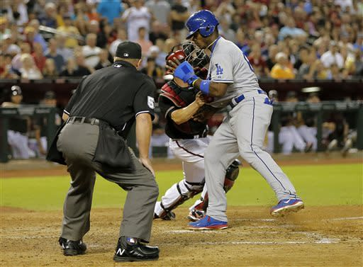 Arizona Diamondbacks catcher Miguel Montero tags out Los Angeles Dodgers' Yasiel Puig as umpire Marvin Hudson looks on during the fifth inning of a baseball game, Tuesday, July 9, 2013, in Phoenix. (AP Photo/Matt York)