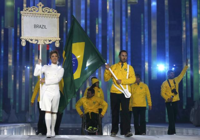Brazil's flag-bearer Andre Pereira (C), leads his country's contingent during the opening ceremony of the 2014 Paralympic Winter Games in Sochi, March 7, 2014. REUTERS/Alexander Demianchuk (RUSSIA - Tags: OLYMPICS SPORT)
