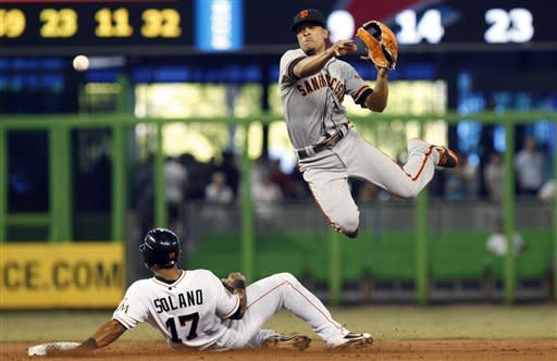 Miami Marlins' Donovan Solano (17) is out at second as San Francisco Giants second baseman Emmanuel Burriss throws to first, where Chris Coghlan was safe in the second inning of a baseball game in Miami, Saturday, May 26, 2012. (AP Photo/Lynne Sladky)