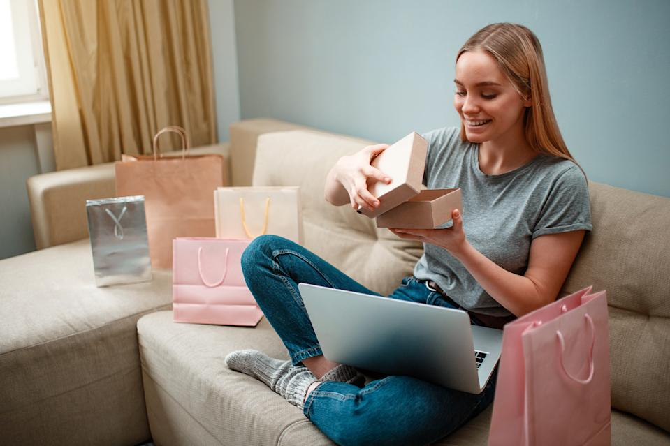 Online shopping Young smiling shopper is unboxing her new parcel and looking into, ordered and delivered by internet