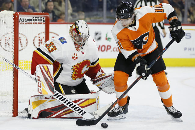 Philadelphia Flyers' Travis Konecny (11) cannot get a shot past Calgary Flames' David Rittich (33) during the second period of an NHL hockey game, Saturday, Nov. 23, 2019, in Philadelphia. (AP Photo/Matt Slocum)