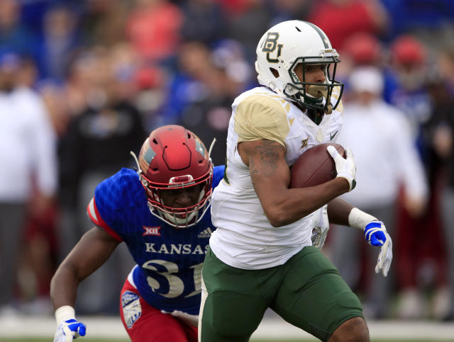 Baylor running back Trestan Ebner (25) gets away from Kansas linebacker Osaze Ogbebor (31) during the first half of an NCAA college football game in Lawrence, Kan., Saturday, Nov. 4, 2017. (AP Photo/Orlin Wagner)