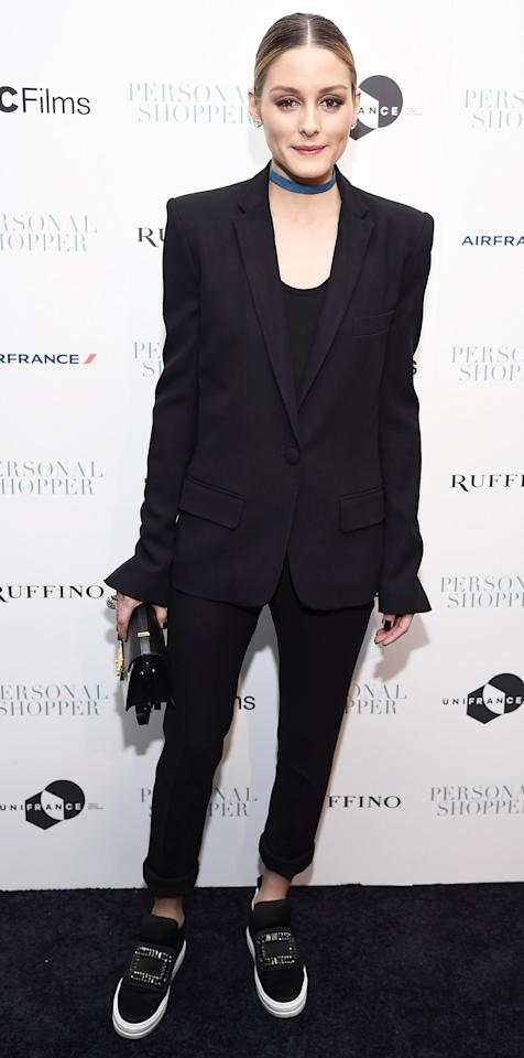 <p>Olivia Palermo wore a boy-borrowed silhouette: a blazer jacket with slight flare cuffs and sneakers revamped with crystal embellishments. The style star finished her look with a black and gold clutch and a blue choker for added color.</p>