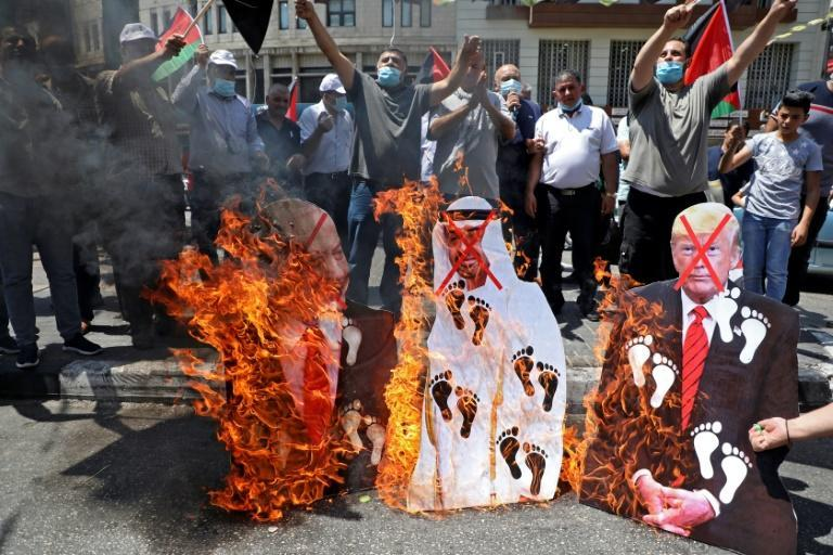 Palestinian protesters burn images of Israeli Prime Minister Benjamin Netanyahu, Abu Dhabi Crown Prince Sheikh Mohammed bin Zayed al-Nahyan, and US President Donald Trump, in the West Bank town of Nablus denouncing the UAE-Israel deal as a betrayal