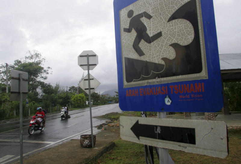In this photo taken Wednesday, April 18, 2012, motorists ride past a sign showing a tsunami evacuation route in Banda Aceh, Aceh province, Indonesia. Residents living in tsunami-scarred Aceh province should prepare themselves for a possible repeat of the 2004 disaster, a leading seismologist said, noting historical data indicates tremendous stresses building up along the explosive fault could unleash again anytime within the next half century. (AP Photo/Heri Juanda)