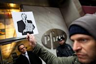 "An Occupy Wall Street protestor holds up a flyer bearing the likeness of former President Ronald Reagan that reads ""Legislative Influence for Sale,"" during a march on the offices of pharmaceutical giant Pfizer, Wednesday, Feb. 29, 2012, in New York. There was a heavy police presence around the 42nd Street area as the demonstration began Wednesday morning outside. (AP Photo/John Minchillo)"