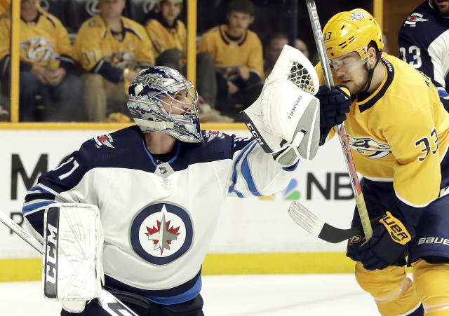 Winnipeg Jets goalie Connor Hellebuyck (37) catches the puck in front of Nashville Predators left wing Viktor Arvidsson (33), of Sweden, during the second period in Game 1 of an NHL hockey second-round playoff series Friday, April 27, 2018, in Nashville, Tenn. (AP Photo/Mark Humphrey)