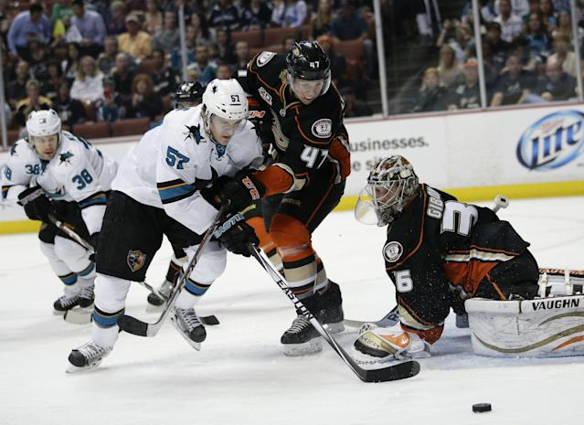 San Jose Sharks' Tommy Wingels, left, and Anaheim Ducks' Hampus Lindholm, of Sweden, scramble for the puck in front of Anaheim Ducks goalie John Gibson during the first period of an NHL hockey game Wednesday, April 9, 2014, in Anaheim, Calif. (AP Photo/Jae C. Hong)