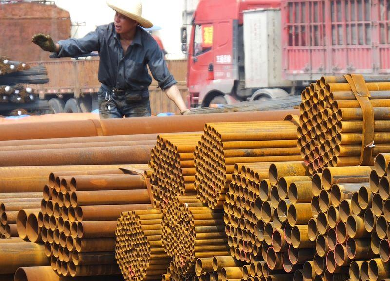 An employee unloads steel products at a market in Yichang