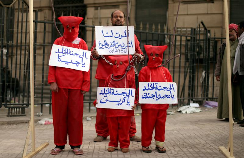 "An Egyptian man with his three children wear red during a symbolic hanging at an anti-government protest in front of Egypt's high court building in downtown Cairo, Friday, Feb. 22, 2013. The Arabic writing on the banners reads, ""death is more honorable for me and my children than poverty and hunger,"" and "" Jeeka, Christy and Mohammed to heaven."" Egypt's president called multi-stage parliamentary elections beginning in April but a key opposition leader warned Friday that the vote may only inflame tensions unless there are serious political talks first.(AP Photo/Khalil Hamra)"