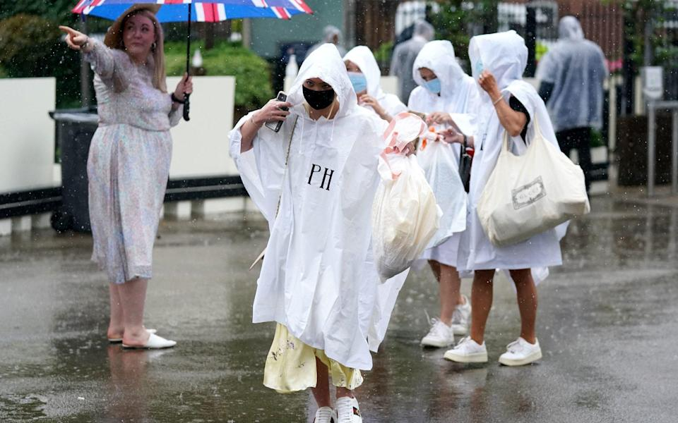 Umbrellas and ponchos were key fashion accessories at Royal Ascot on day four - PA