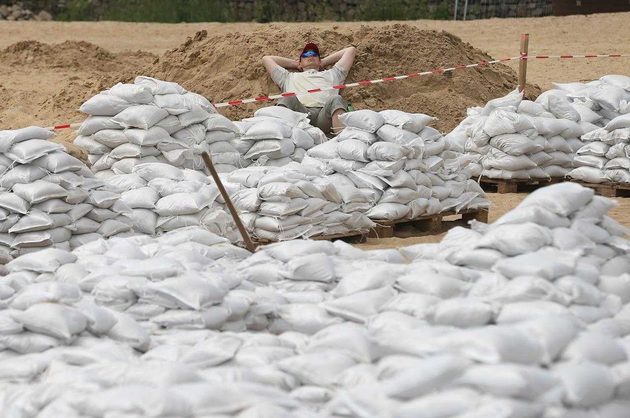 WITTENBERGE, BRANDENBURG - JUNE 11: A local resident and volunteer, who said he has been filling sandbags on day and night shifts since last week, takes a break among sandbags filled by volunteers to strengthen dykes against the swollen Elbe river on June 11, 2013 in Wittenberge, Germany. Authorities are revising their river level estimates downward following the bursting of a dyke upstream that sent floodwaters into fields and nearby villages. Germany is experiencing floods that in some regions are the worst in recorded history and at least seven people have died. (Photo by Sean Gallup/Getty Images)