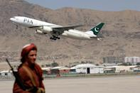 A Taliban fighter stands guard as a Pakistan International Airlines plane, the first commercial international flight to land since the Taliban retook power last month, takes off from Kabul airport to return to Islamabad (AFP/Karim SAHIB)