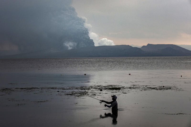BALETE, PHILIPPINES - JANUARY 13: A resident fishes at a lake as Taal Volcano erupts on January 13, 2020 in Balete, Batangas province, Philippines. The Philippine Institute of of Volcanology and Seismology raised the alert level to four out of five, warning that a hazardous eruption could take place anytime, as Manila's international airport suspended flights and authorities began evacuating tens of thousands of people from the area. (Photo by Ezra Acayan/Getty Images)