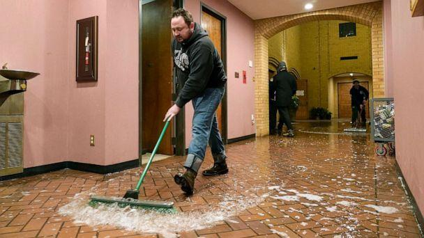 PHOTO: Father John Szatkowski of St. Paul The Apostle Church sweeps water from a broken water line out of his church in Richardson, Texas, Feb. 17, 2021, after a winter storm brought cold temperatures. (Tony Gutierrez/AP)