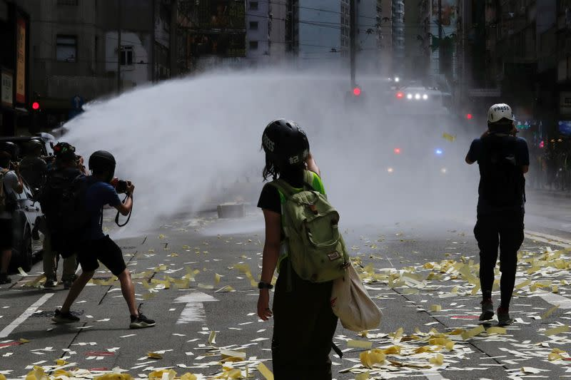 Riot police use water cannon to disperse anti-national security law protesters during a march at the anniversary of Hong Kong's handover to China from Britain in Hong Kong