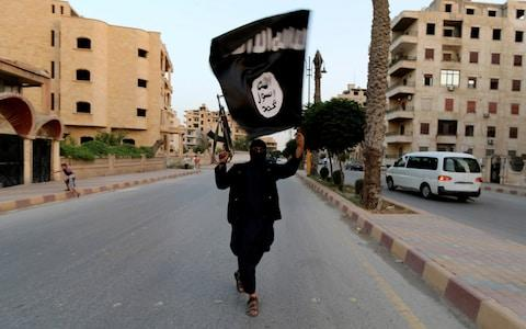 A member loyal to the Islamic State in Iraq and the Levant (ISIL) waves an ISIL flag in Raqqa June 29, 2014 - Credit: Reuters